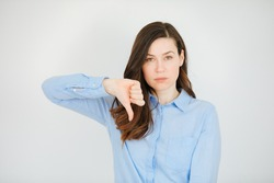Discontent  woman shows diapproval sign, keeps thumb down, expresses dislike, frowns face in discontent.white background. Body language concept. Dissatisfaction and anger