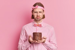 Discontent young European man has bob hairstyle looks sullen at camera feels sad as celebrates birthday alone poses with cake wears headband striped shirt bowtie isolated over pink background.