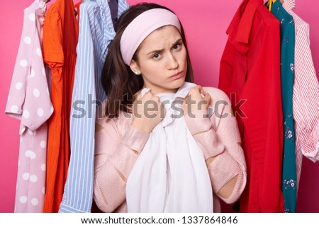 Discontent young female embraces white blouse. Beautiful woman wears rose sweater and hair band. Upset girl with lots clothes in wardrobe. Charming lady isolated over pink background. Fasion concept.