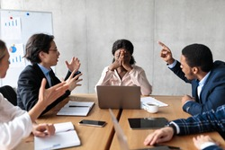 Discontented Coworkers Shouting At Unhappy Victimized Businesswoman Sitting At Table In Modern Office. Adult Bullying At Work, Conflicts And Disagreement, Business Communication Problems Concept
