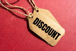 Discount- a paper price tag with a twine against red background, shopping opportunity and consumerism concept
