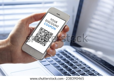 Discount coupon with QR code on smartphone with laptop in background