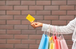 Discount for shop and payment for purchase. African american woman with multicolored packages gives credit card, free space