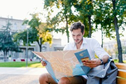 Discovering new places. Close-up of handsome young man holding map and looking at it while sitting on a bench. Young man with a map outdoors. Lost tourist looking at city map on a trip