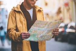 Discovering new places. Close-up of handsome young man holding map and looking at it while standing on the city street