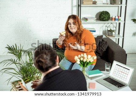 Discuss your thoughts. Cute plump female actively gesticulating while speaking with psychologist