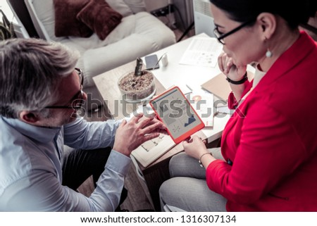 Discussing a project. Adult grey-haired businessman wearing eyeglasses discussing a project with a manager #1316307134