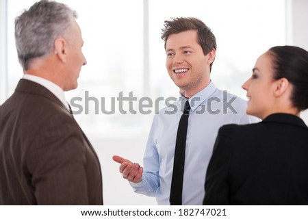 Discussing a successful project. Three cheerful business people discussing something while standing close to each other