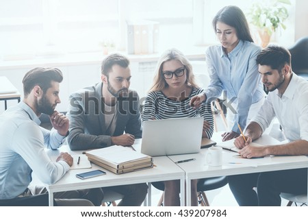 Discussing business issues. Group of young business people sitting at the office desk and discussing something while looking at laptop together #439207984