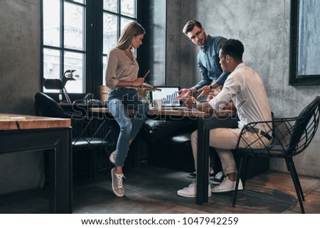 Discussing business issues. Group of young confident business people analyzing data using computer while spending time in the office #1047942259
