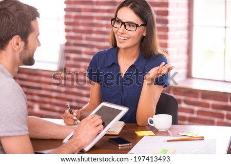 Discussing business. Two cheerful business people in casual wear talking and gesturing while sitting at the table