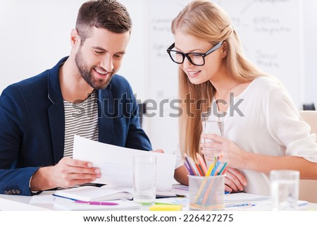 Discussing contract together. Two confident business people in smart casual wear sitting together at the table and discussing something while looking at the document