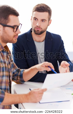Discussing project. Two confident business people in smart casual wear sitting together at the table and discussing something