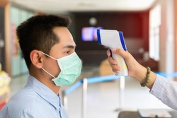 Disease control experts use an Infrared thermometer equipment to check the temperature on the forehead and use alcohol gel to screen the patients addicted to Covid-19 before entering the building.