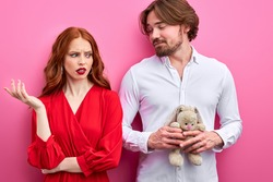 disgruntled woman shocked by immature man holding toy in hands, he is in love with her, man and woman in party clothes. isolated on pink background