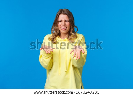 Disgusted childish cute blond girl in yellow hoodie show tongue from aversion, shrugging and raise hands in dismay, disappointed after tasting something bad, smell disgusting reek, blue background
