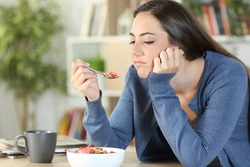 Disgusted woman eating breakfast cereal bowl looking at spoon bored sitting at home