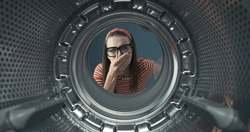 Disgusted woman looking into her smelly washing machine, she is holding her nose, point of view shot