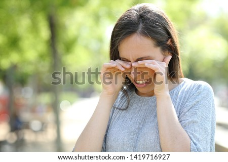 Disgusted woman rubbing her eyes standing outdoors in a park #1419716927