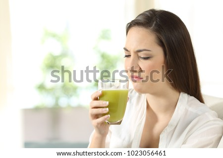 Disgusted woman tasting a vegetable juice with bad flavor sitting on a couch in the living room at home