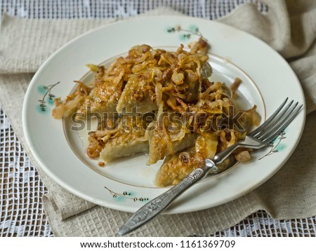Dish Lithuanian, Polish, Belarusian cuisine knows as kopytka or kapytki - rhombuses potato with fried onions on old keramic plate with lace napkin. Close up #1161369709