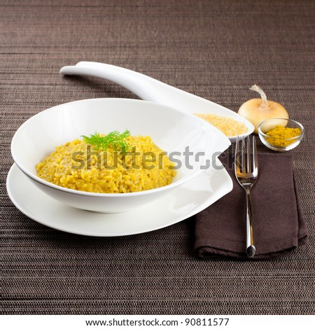 Dish of cooked saffron and curry rice with raw ingredient on side over a brown tablecloth