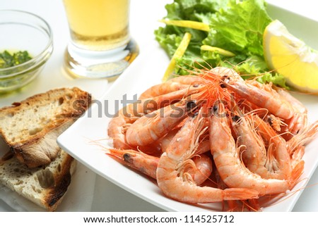 dish of fresh boiled prawns seasoned with sea salt, with lettuce, some bread and beer