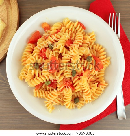Dish of Italian pasta fusilli with fresh tomato sauce, capers and ...