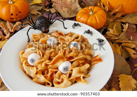 Dish of noodle brains and eyeballs with halloween spiders and a jock-o-lantern