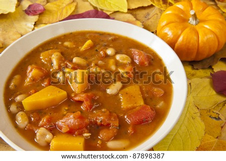 Dish of pumpkin soup  surrounded by colorful fall leaves
