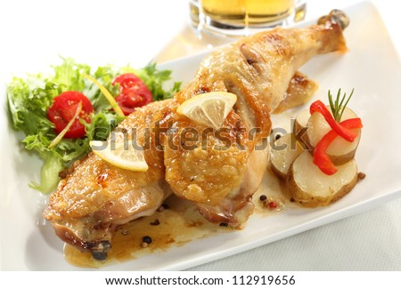 Dish of two roasted chicken legs isolated on white (left top), beer glass on background. - stock photo