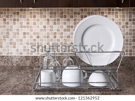 Dish rack with white plates and cups on kitchen countertop.