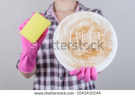 Dish washer concept spot symbol child kid teen age boring mood family dinner ask play work hard concept. Close up photo of girl holding dirty white plate with unhappy face isolated on gray background