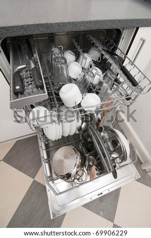 Dish washer with clean and shiny dishes and kitchenware
