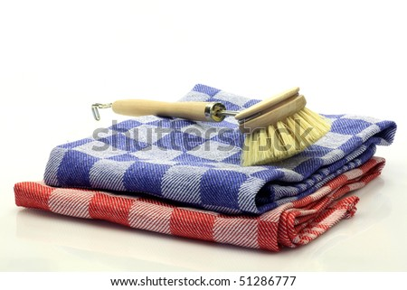 dish washing brush on vintage towels on a white background