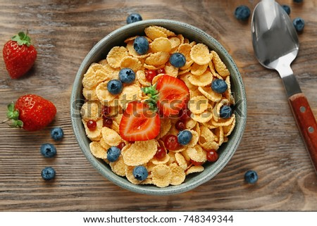 Dish with cornflakes and berries on table #748349344