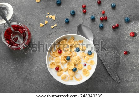 Dish with cornflakes and milk on table #748349335
