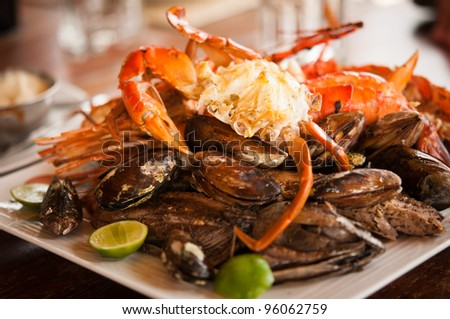 Dish with crab and mussels. Selective focus on the crab's body.