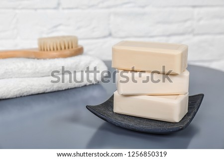 Dish with soap bars on grey table. Space for text