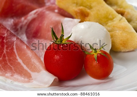 Dish with typical Italian food. Raw ham, mozzarella cheese, cherry tomatoes and focaccia pizza