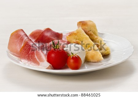 Dish with typical Italian food. Raw ham, mozzarella cheese, cherry tomatoes and focaccia pizza - stock photo