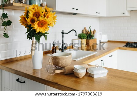 Dishes and utensils on kitchen table, ready to cook. white simple modern kitchen in scandinavian style, kitchen details, wooden table, sunflowers bouquet in vase on the table