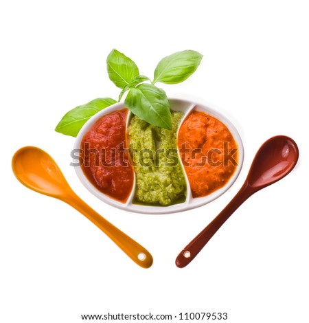 dishes for sauces with three different kinds of sauces, a branch of basil and ceramic spoon isolated on white background