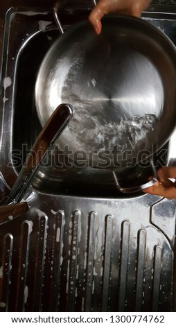 Dishes in metal sink #1300774762