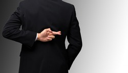 Dishonest businessman telling lies, lying male entrepreneur holding fingers crossed behind his back