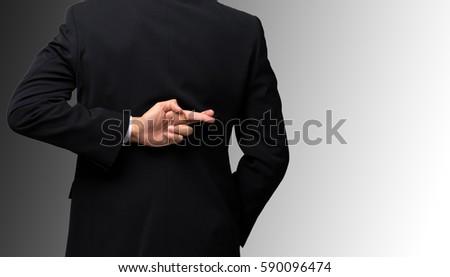 Dishonest businessman telling lies, lying male entrepreneur holding fingers crossed behind his back ストックフォト ©