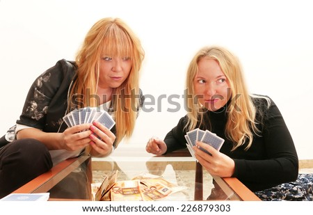 dishonest friend cheating her girl friend while gambling for money, playing card games
