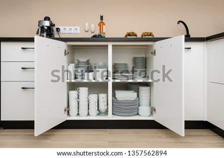 Dishware storage cabinet with open doors, white plates, bowls cups and other china crockery inside, front view Stock photo ©