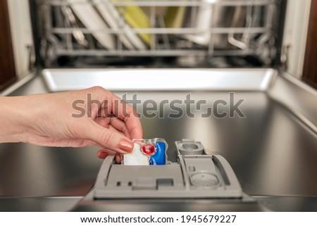 Dishwasher capsule, dishwasher tablets woman puts the capsule in the dishwasher before washing the pasta
