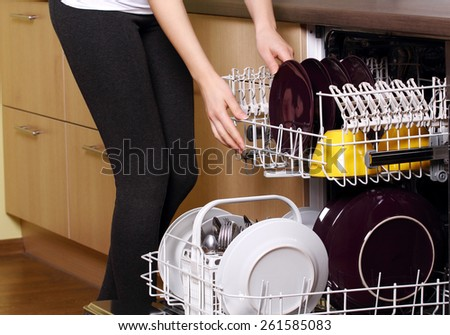 Dishwasher. Young woman in kitchen doing housework. Puling out dishes from dishwasher